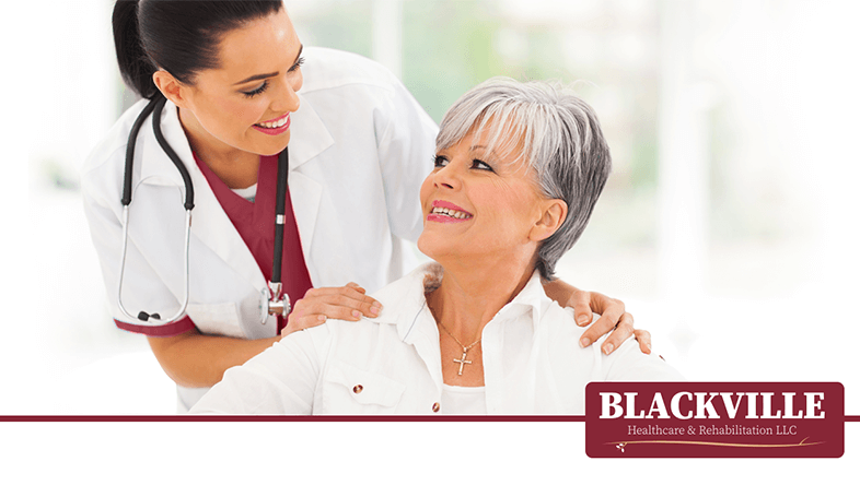 Nurse Smiling at an Elderly Woman at a Nursing Rehabilitation Centerwith the Blackville Healthcare & Rehabilitation Logo